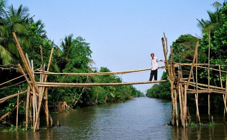 A man crossing the monkey bridge with trees surrounding