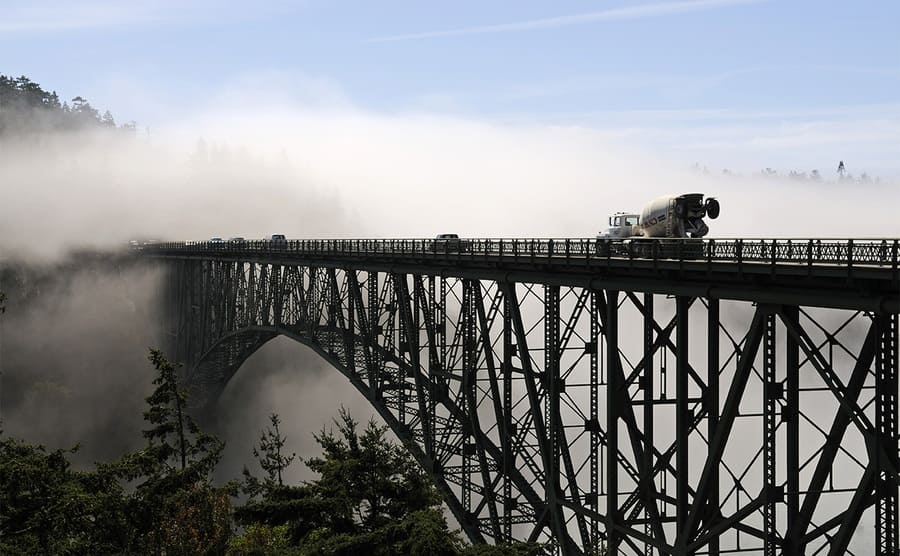 A truck and cars driving over the bridge with fog surrounding it