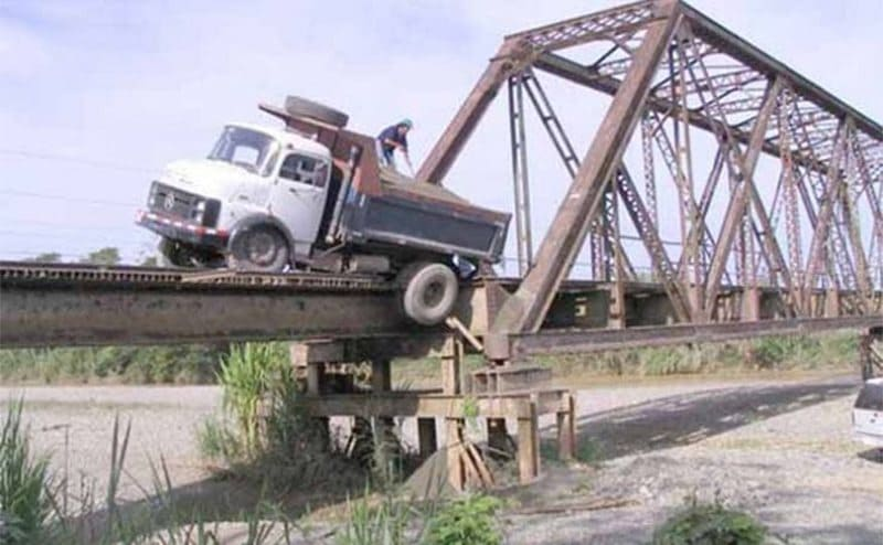 A truck crossing the bridge with one wheel off the edge