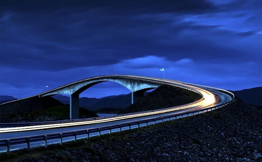 The Storseisundet Bridge at night with lights blurred down the road
