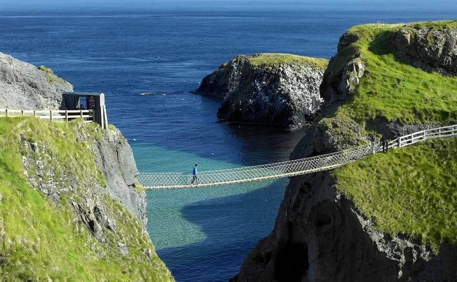 A man walking over the bridge made of rope over the ocean
