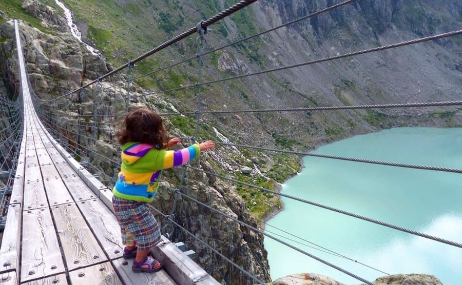 A little girl holding on to the side of the Trift Bridge
