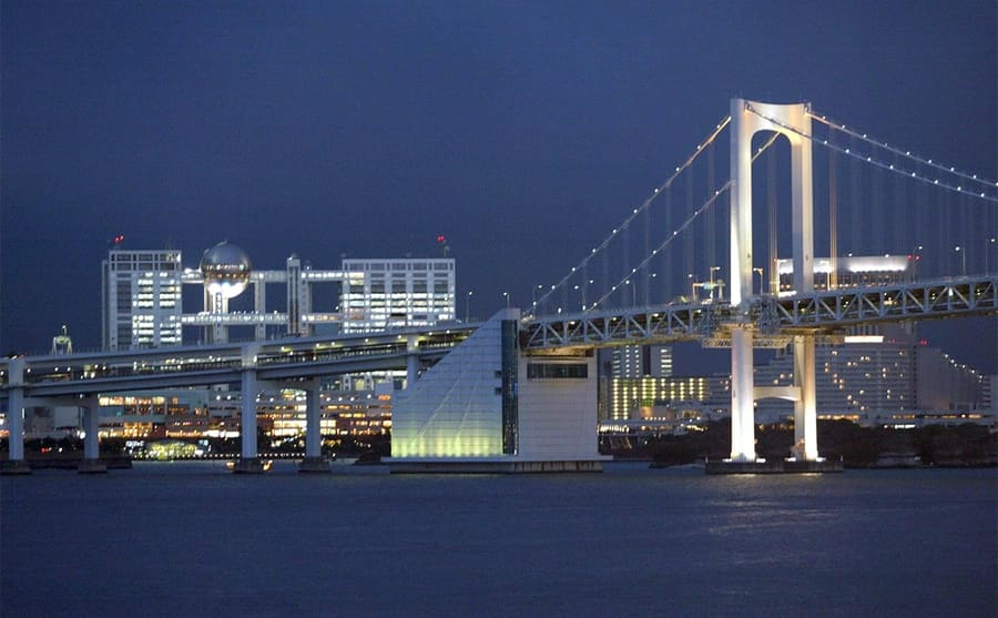 A photograph of the white lit up Akashi Kaikyo suspension bridge in the evening