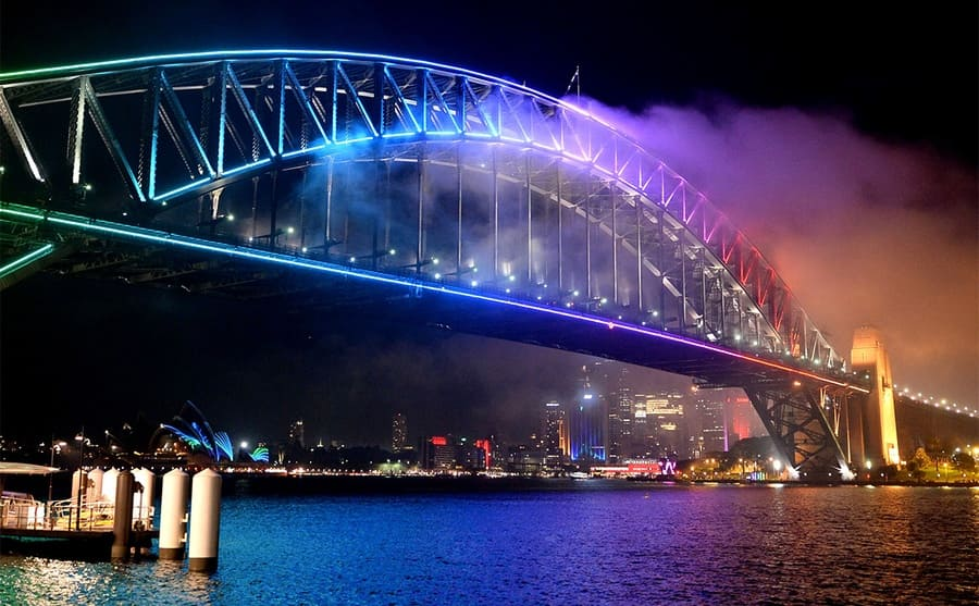 The Sydney Harbour Bridge lit up at night with the Opera House in the background