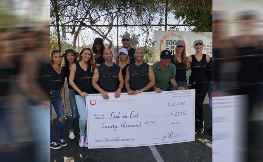 The Oppenheim group at an event for Food on Foot holding a $20,000 check