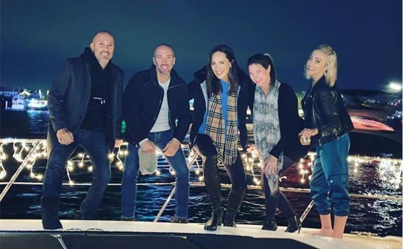 Brett and Jason with three of the girls posing on a yacht