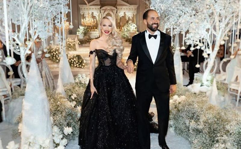 Christina and her husband posing in the aisle on their wedding day