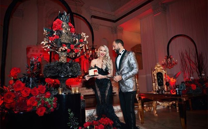 Christina and her husband holding a slice of wedding cake surrounded by black accents and red roses