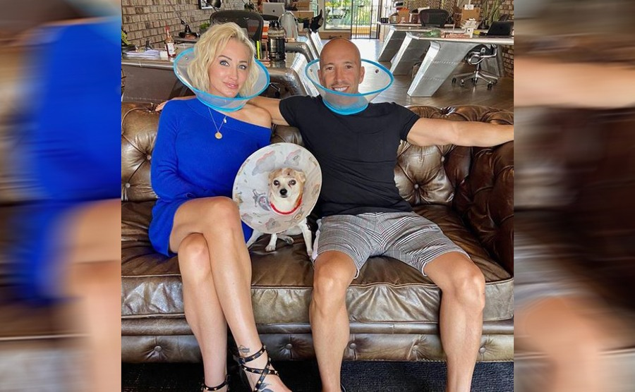 Mary and Jason wearing cones around their heads while sitting on the couch with their dog, who is also wearing a cone around his head