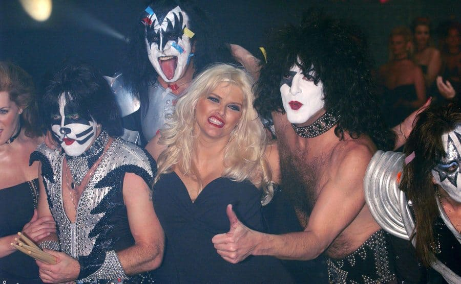 Anna Nicole Smith posing at an event with the members of Kiss