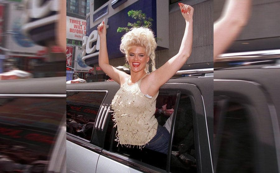 Anna Nicole Smith smiling sitkcing her body with her hands up out of a limosoine window