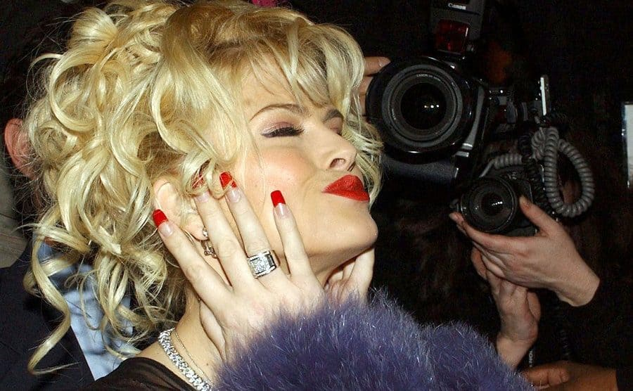 Anna Nicole Smith posing with paparazzi surroundeing her
