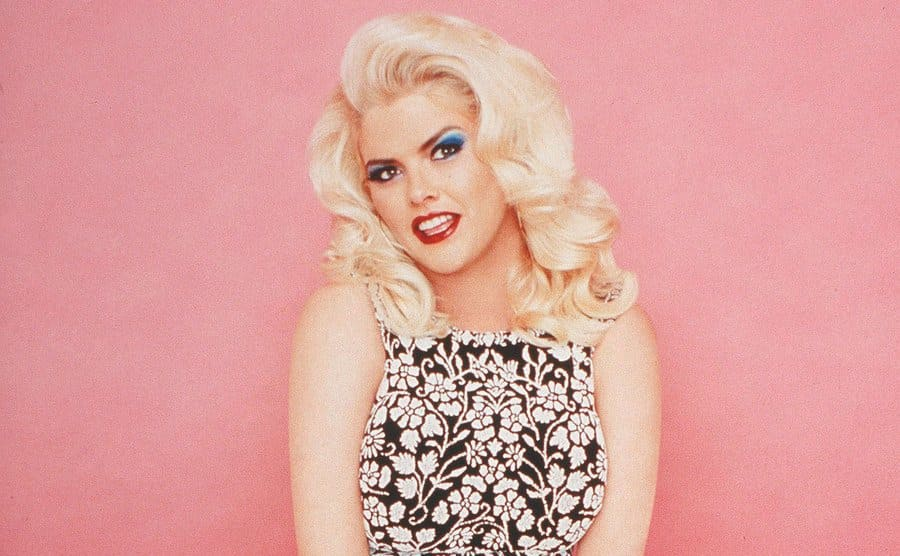 Anna Nicole Smith posing in front of a pink backdrop in a promotional shot for her tv show
