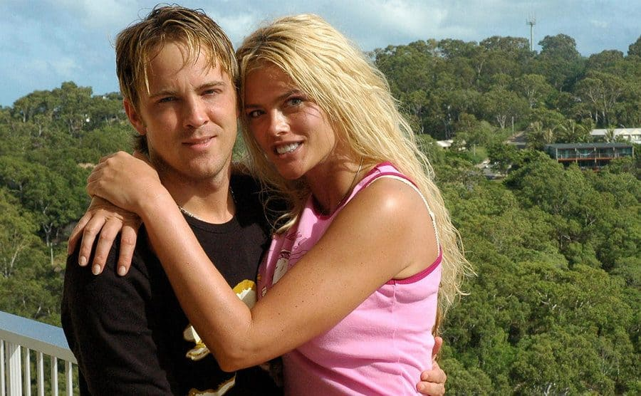 Larry Birkhead and Anna Nicole Smith in front of a view of tree covered hill