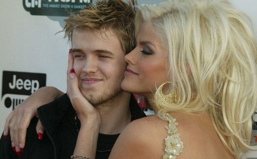 Anna Nicole Smith smiling lovingly while posing with her son Daniel on the red carpet in 2004