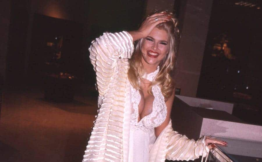 Anna Nicole Smith holding her head while walking around outside of an event in 2004