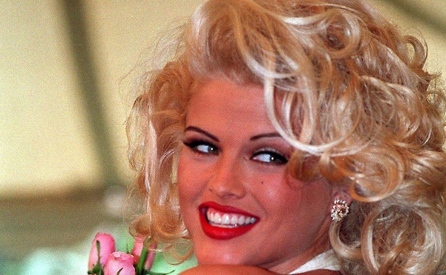 Anna Nicole Smith posing with pink roses looking back over her shoulder