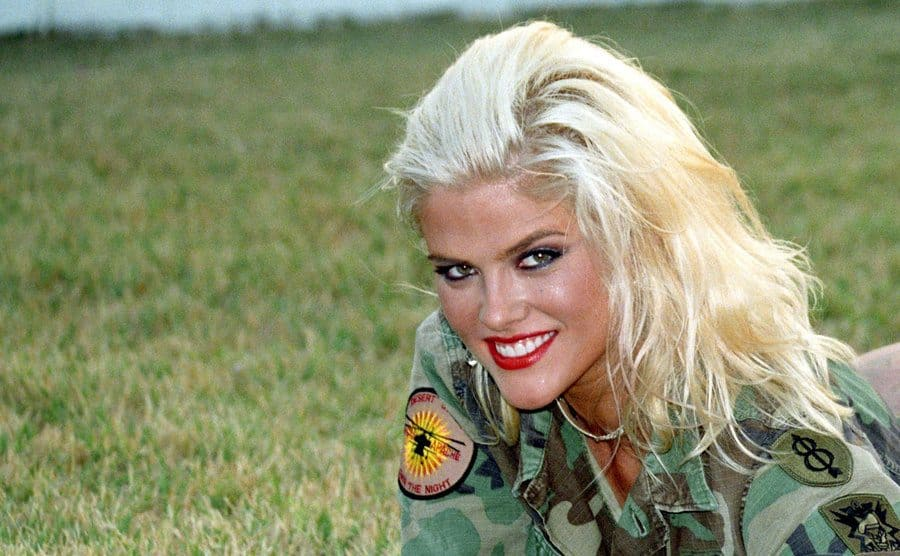 Anna Nicole Smith posing in the grass for a photoshoot 2003