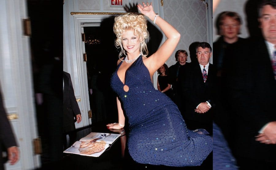 Anna Nicole Smith waving on top of a piano