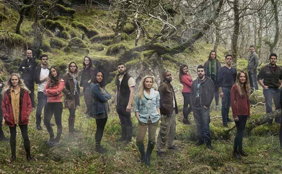 The cast of Eden posing together in the woods