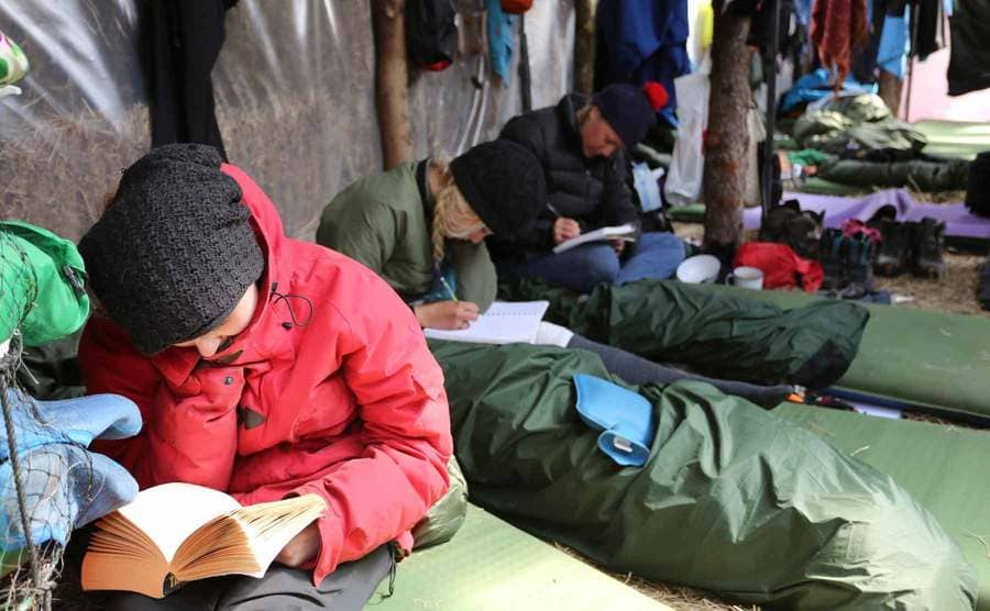 Contestants reading and writing letters home from their sleeping bags