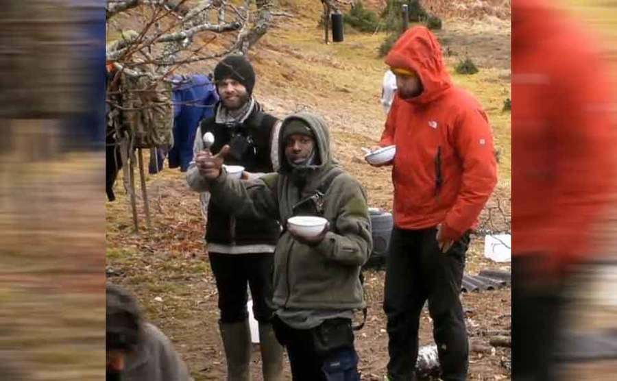 Three contestants hanging around in warm gear holding bowls and spoons