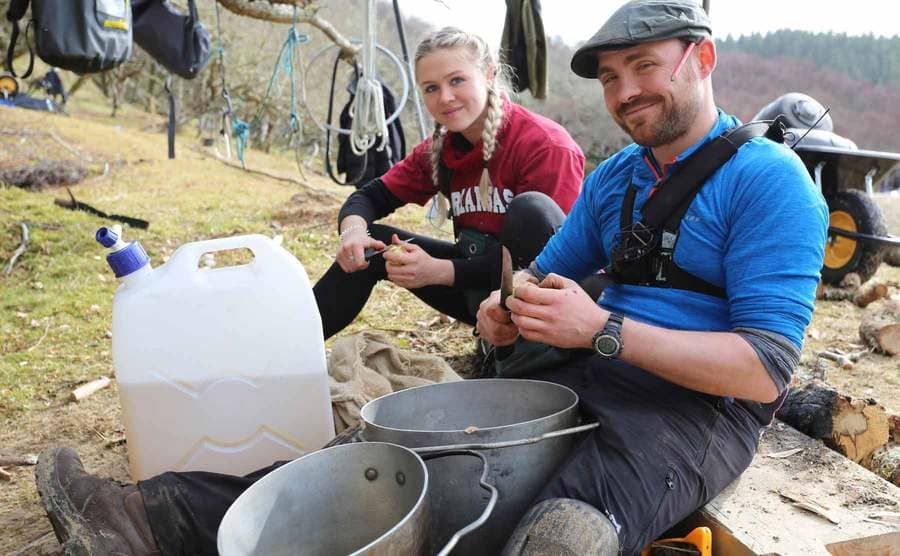 Two contestants peeling potatoes in front of a large jerrycan of water and two large pots