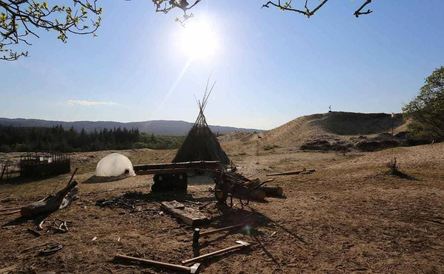 The empty site with a teepee, small tent, and wooden logs