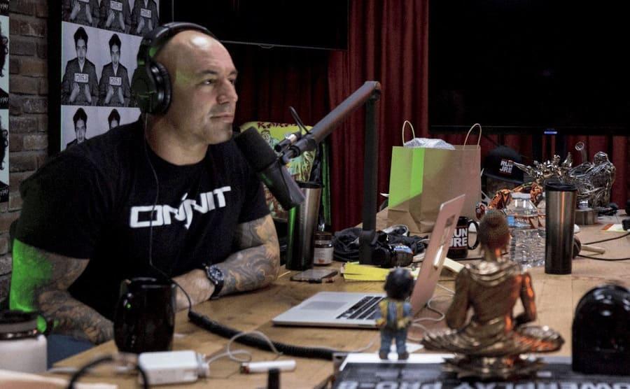 Joe Rogan sitting behind his podcast desk