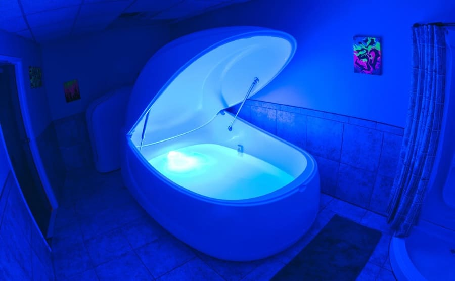 A sensory deprivation tank filled with water with a small blue light on
