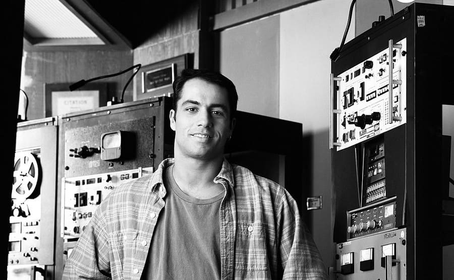 Joe Rogan standing in front of radio equipment on the show NewsRadio