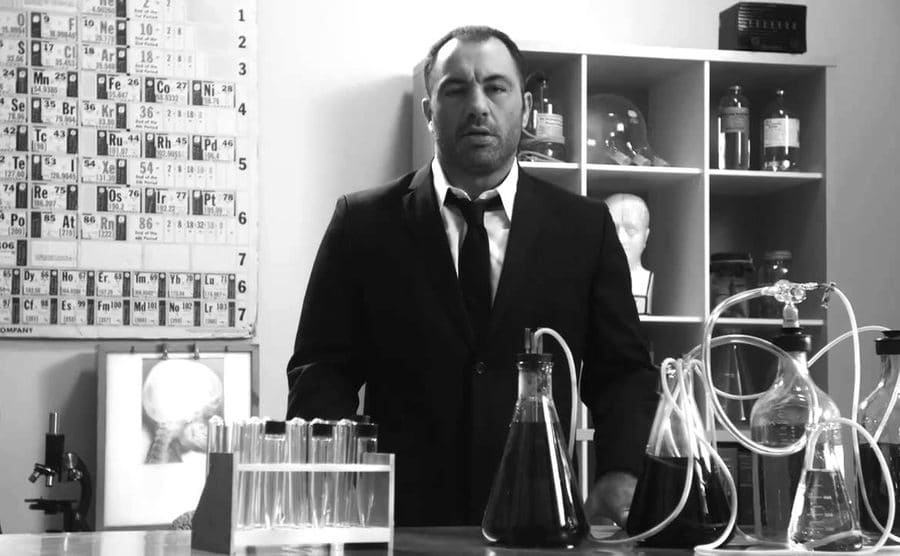 Joe Rogan standing in front of a table with beakers and the periodic table of elements behind him on the wall
