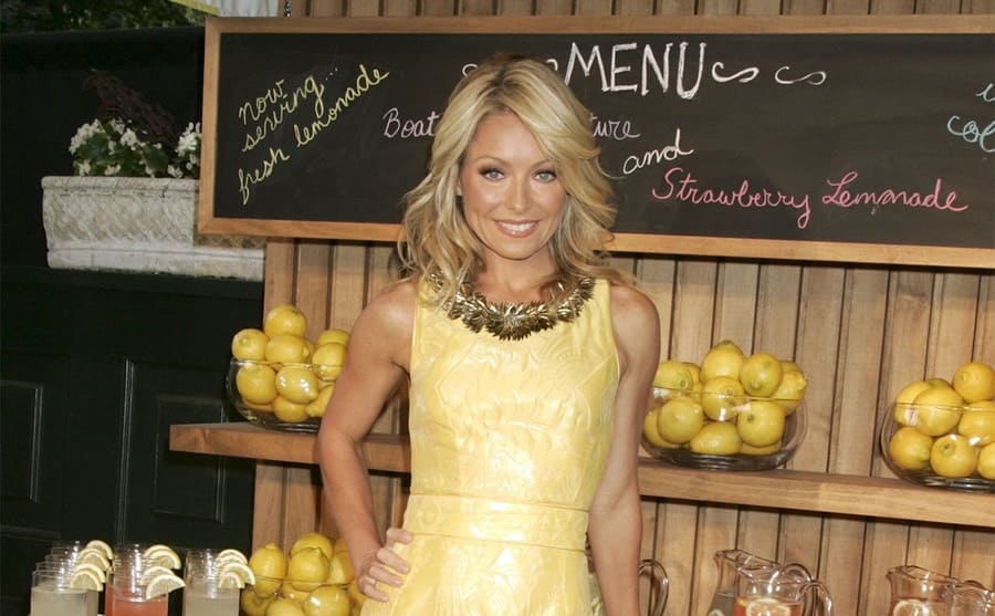 Kelly Ripa standing in a lemonade stand