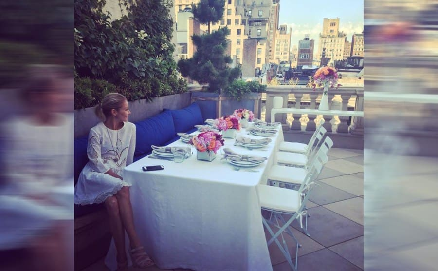 Kelly Ripa sitting on her larch balcony at a long set dinner table
