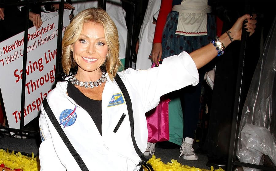 Kelly Ripa posing in a NASA Halloween outfit with her left arm out and tattoo showing