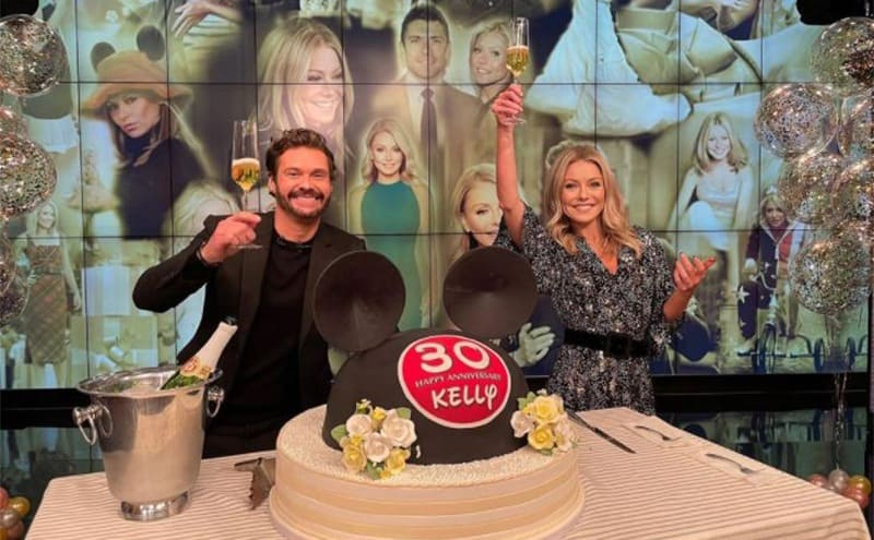 Ryan and Kelly in front of a 30th Anniversary Cake on the set of Live with Kelly and Ryan