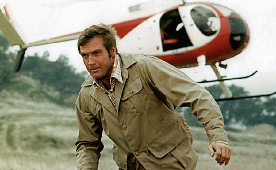 Lee Majors in front of a helicopter