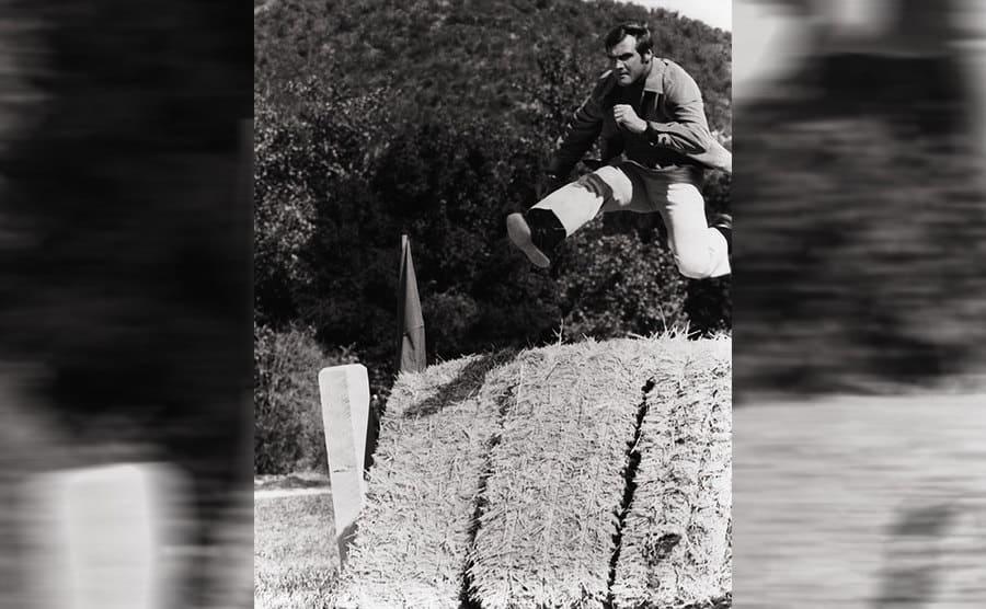 Lee Major jumping over a haystack