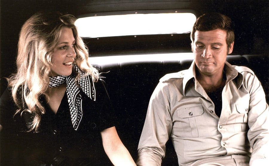 Lindsay Wagner and Lee Majors sitting in a car and holding hands