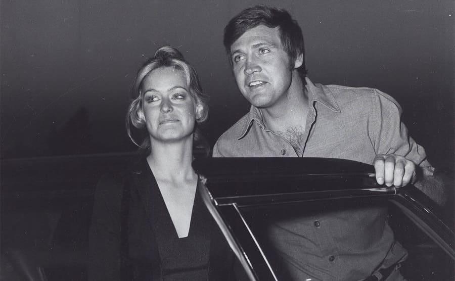 Farrah Fawcett and Lee majors standing in a convertible car