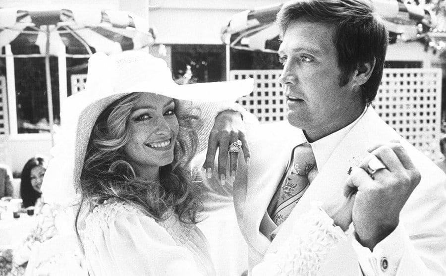 Lee Majors and Farrah Fawcett wearing white and dancing
