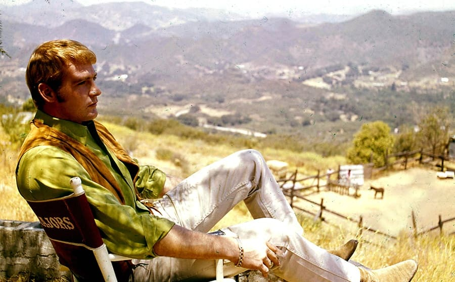 Lee r Majors sitting in a director's chair looking at the valley