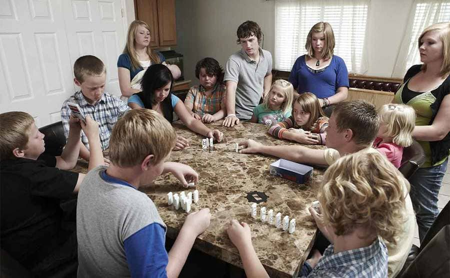 All of their kids playing dominos at the kitchen table