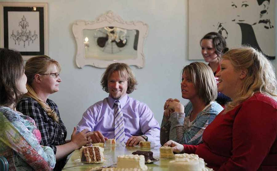 Kody sitting at a table tasting cake with his four wives
