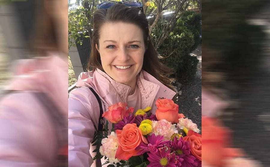 Robyn Brown holding a bouquet of flowers for a selfie outdoors
