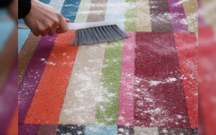 Bicarbonato de sodio esparcido sobre una alfombra que está siendo cepillada.