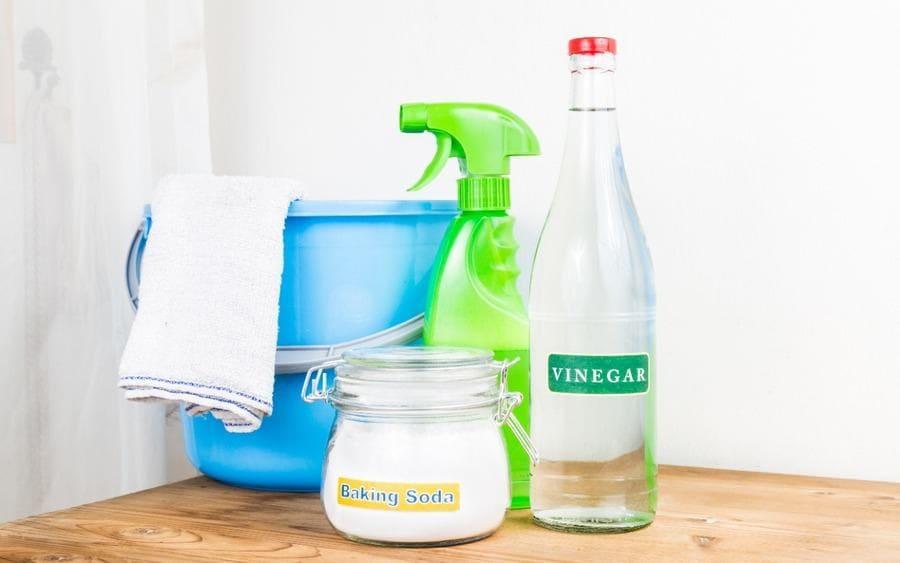 Botella de Vinagre y frasco de bicarbonato de sodio junto a vaso con una mezcla