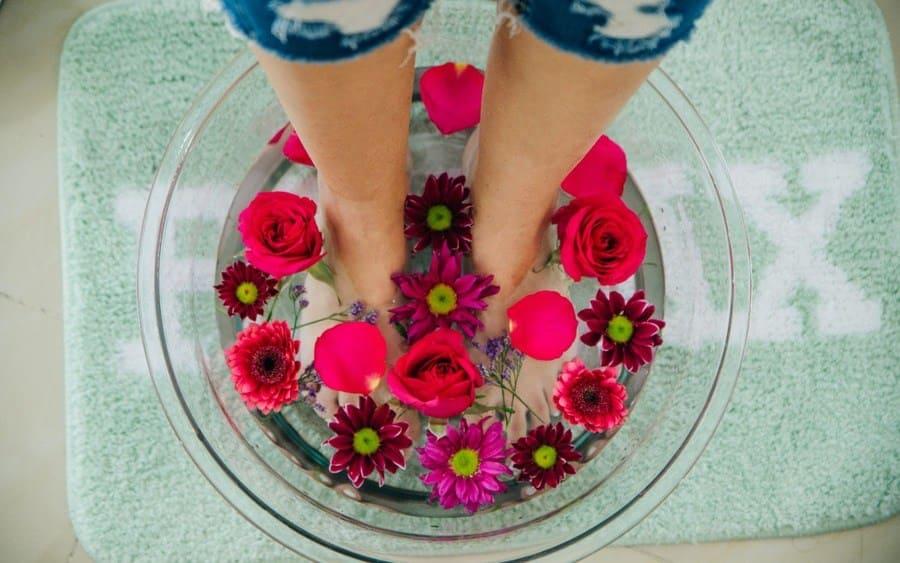 Pies encima de un recipiente con agua y flores