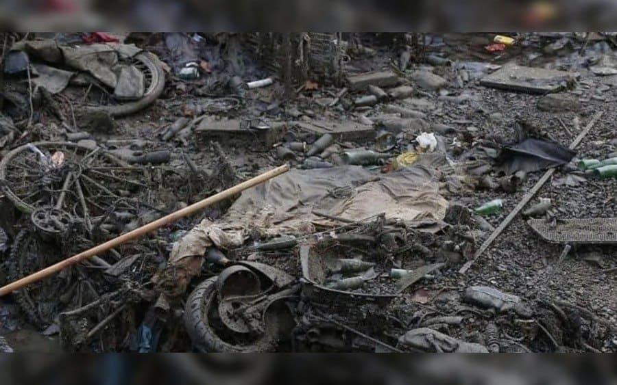 Escombros de bicicletas, botellas y desechos tirados.