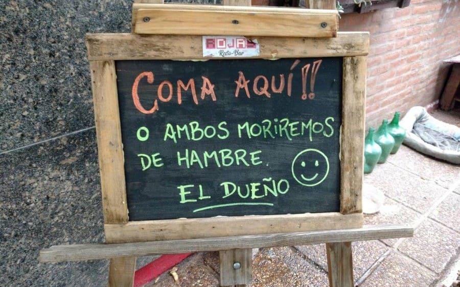 Cartel que lee: Coma aquí o ambos moriremos de hambre, el Dueño.